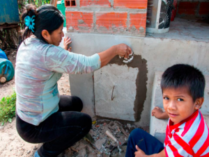 Elena learns how to cement her chamber door. After learning how to mix cement she made 3 grey water filters in her house.